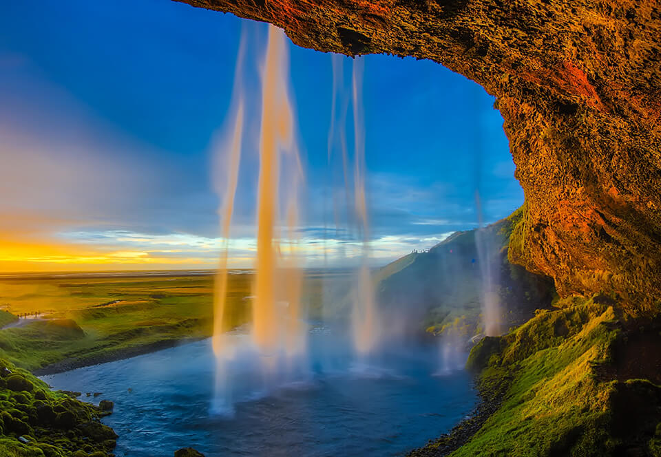 Caves and waterfalls opening to the view of a field with sunlight shining bright.