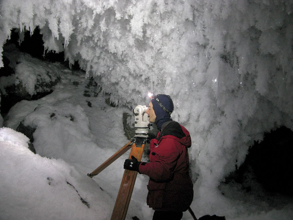 Aaron Curtis, from NCKRI and a New Mexico Tech student, is seen here giving the first systematic survey of ice caves on Mount Erebus.