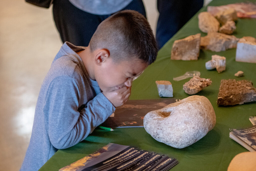 A child looking through a microscope to look closer at a rock formation of a cave in the NCKRI Cave Discovery Zone.