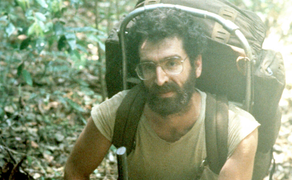 A young Dr. George Veni backpacking to a cave